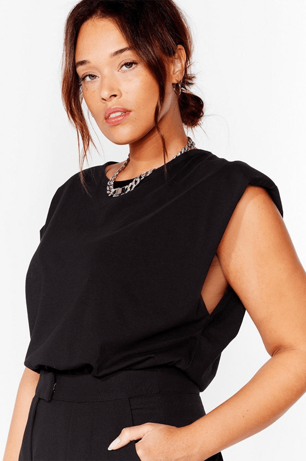 A plus-size model wearing a shoulder pad tee.