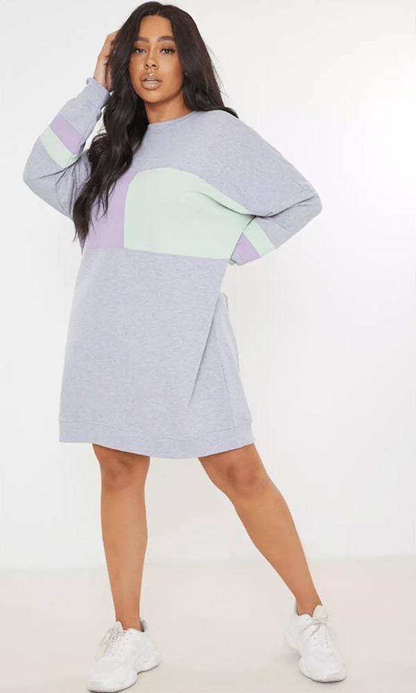 A plus-size model wearing a gray colorblock sweatshirt dress.