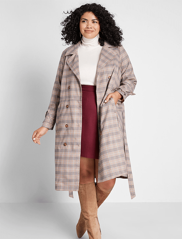 A plus-size model wearing a plaid trench coat.