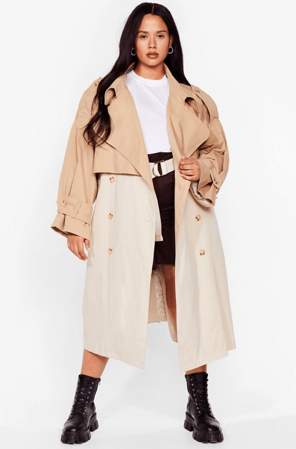 A plus-size model wearing a beige colorblock trench coat.