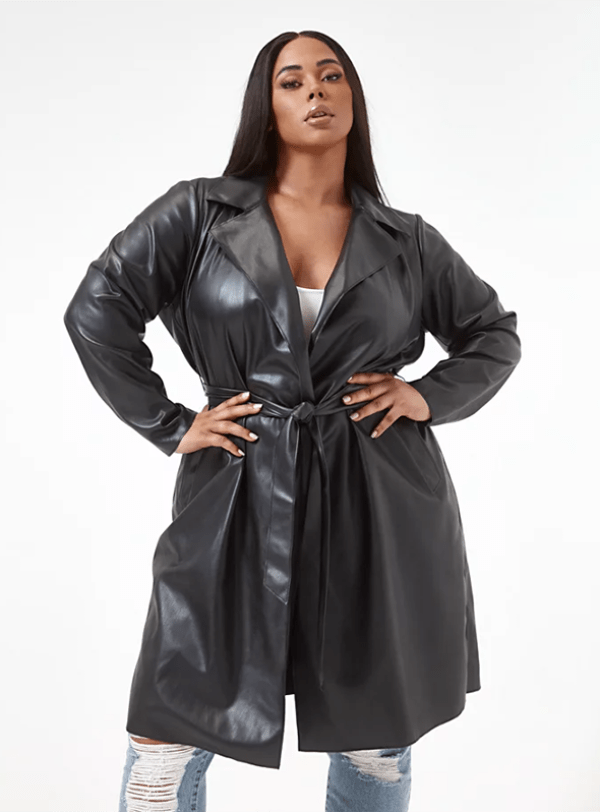 A plus-size model wearing a black leather trench coat.