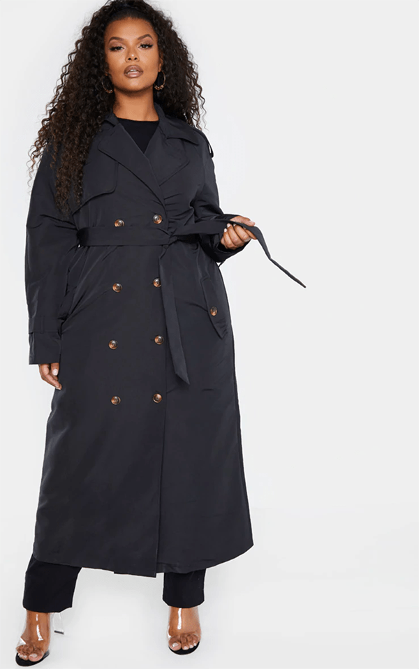 A plus-size model wearing a black trench coat.