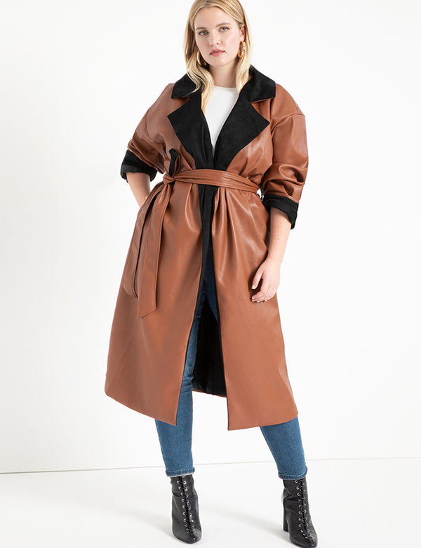 A plus-size model wearing a brown leather trench coat.