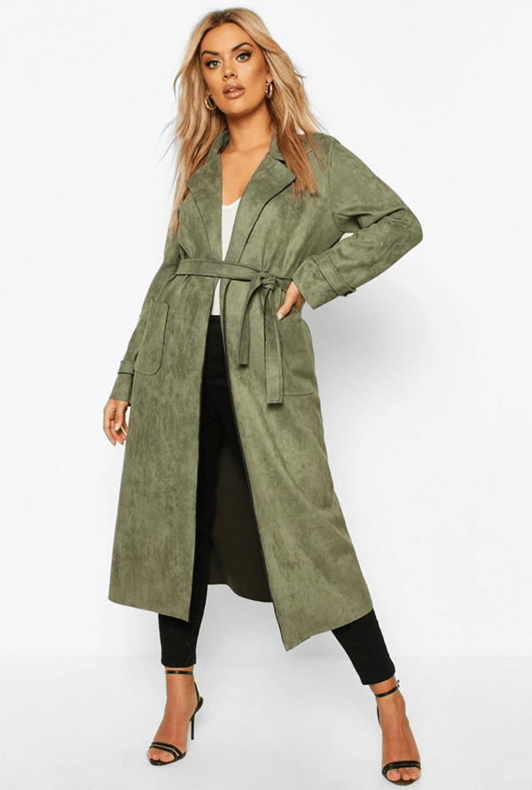 A plus-size model wearing an olive suede trench coat.