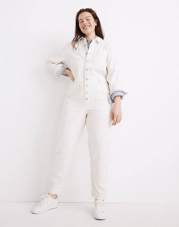 A model wearing a plus-size utility jumpsuit in white.