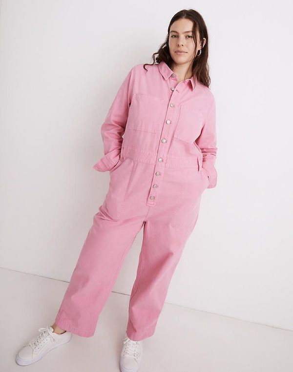 A model wearing a plus-size utility jumpsuit in pink.