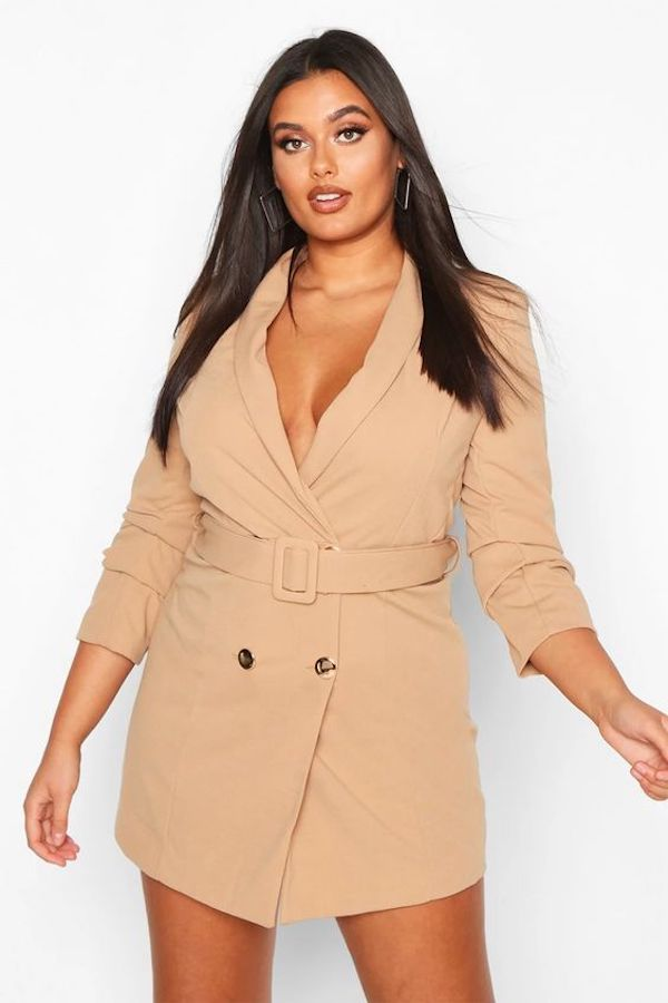 A model wearing a plus-size blazer dress.