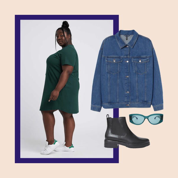 A plus-size model wearing a t-shirt dress, denim jacket, sunglasses, and black booties.