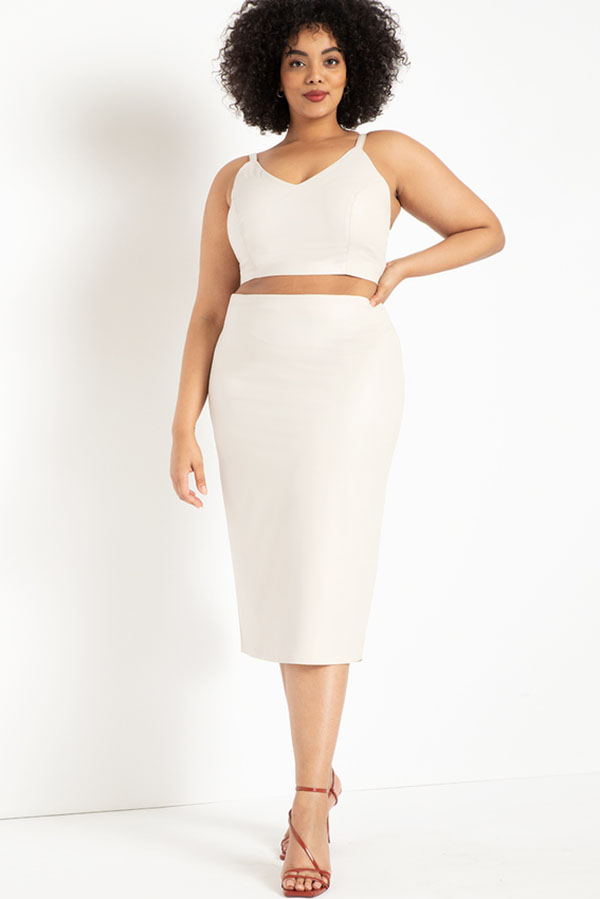 A plus-size model wearing a white leather midi skirt.