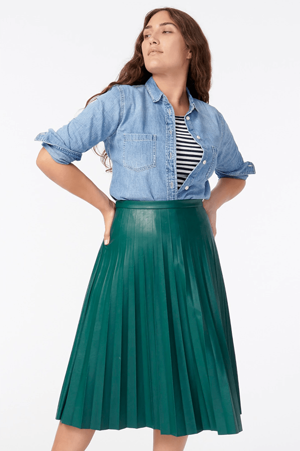 A plus-size model wearing a green pleated leather midi skirt.