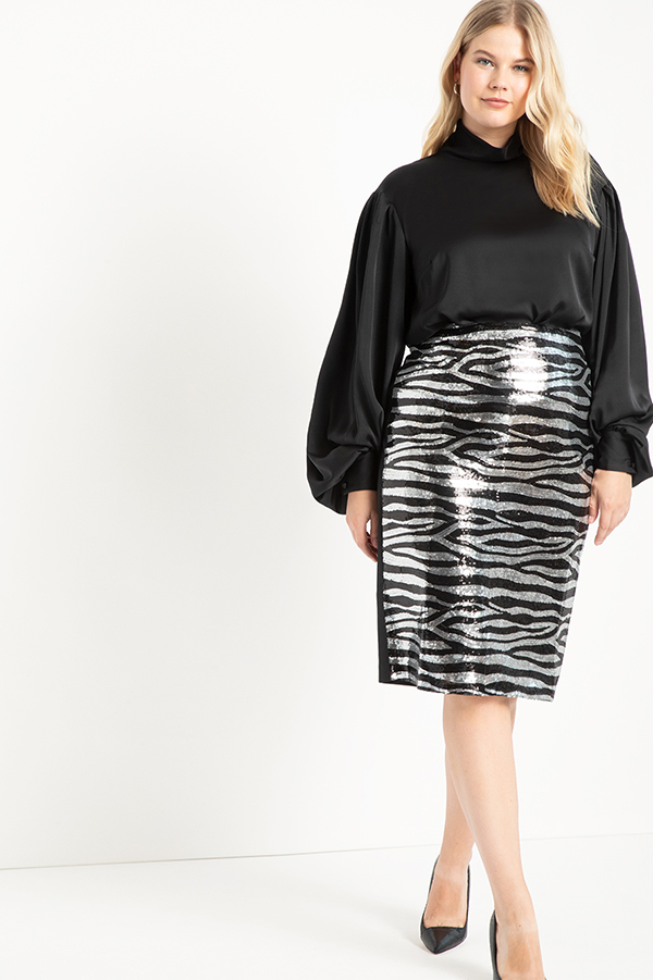 A plus-size model wearing a sequin animal print pencil skirt.