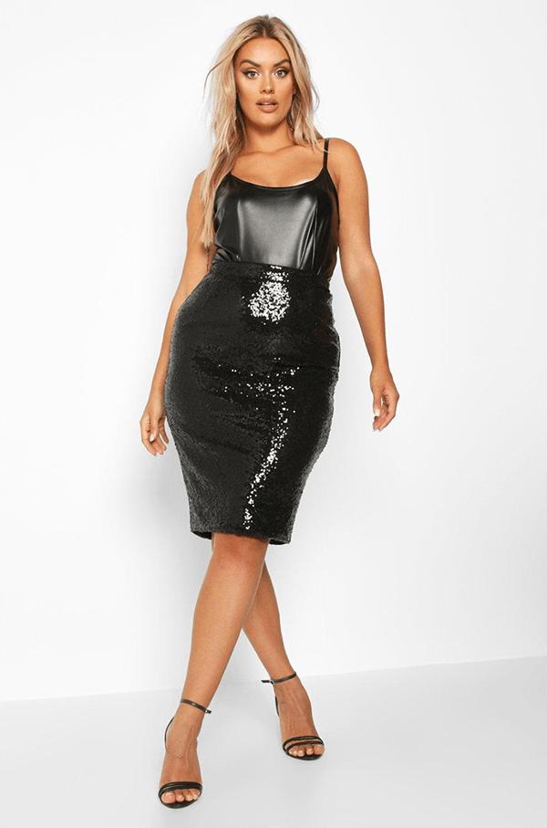 A plus-size model wearing a black sequin pencil skirt.