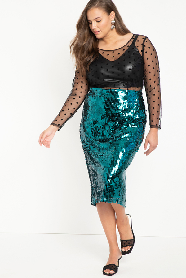 A plus-size model wearing a teal sequin midi skirt.