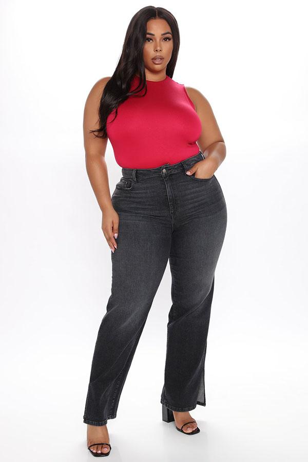 A plus-size model wearing black split-hem jeans.