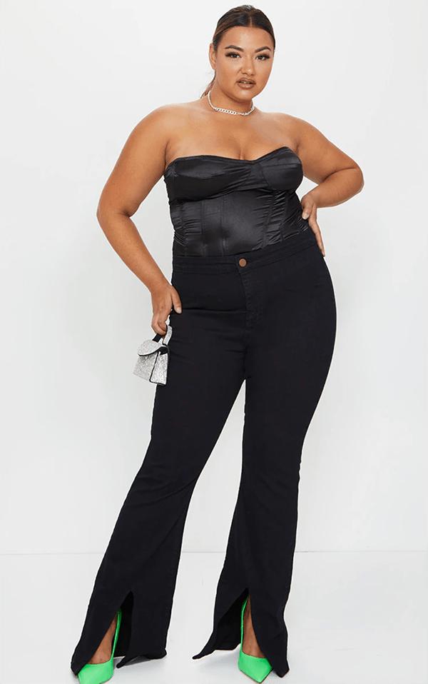 A plus-size model wearing black split-hem flare jeans.