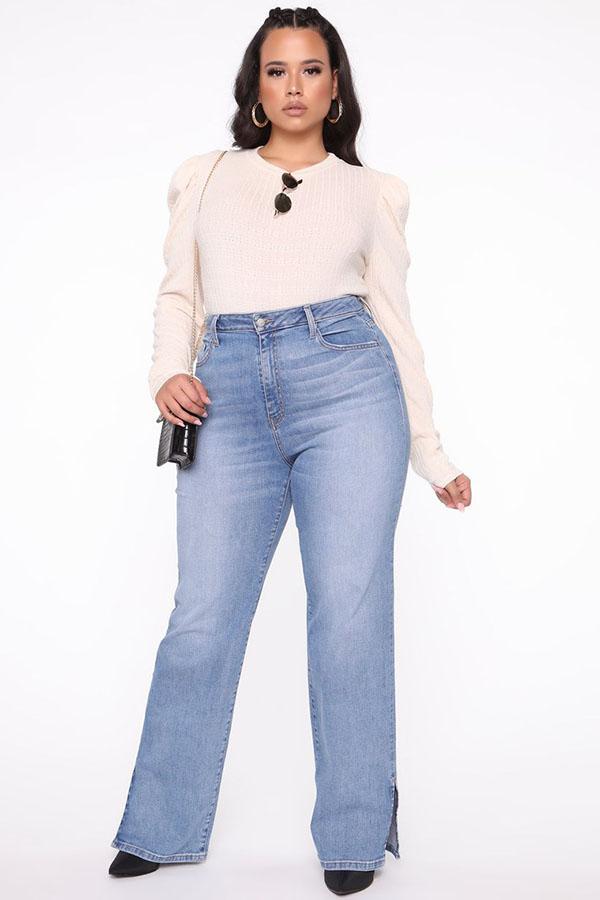 A plus-size model wearing light-wash split-hem jeans.