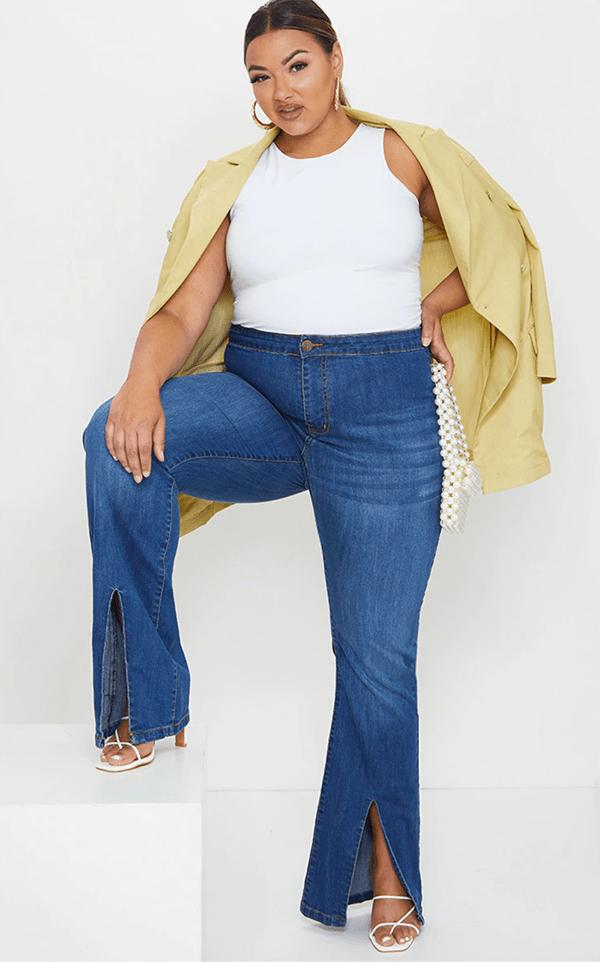 A plus-size model wearing split-hem flare jeans.