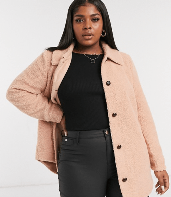 A plus-size model wearing a light pink teddy jacket.