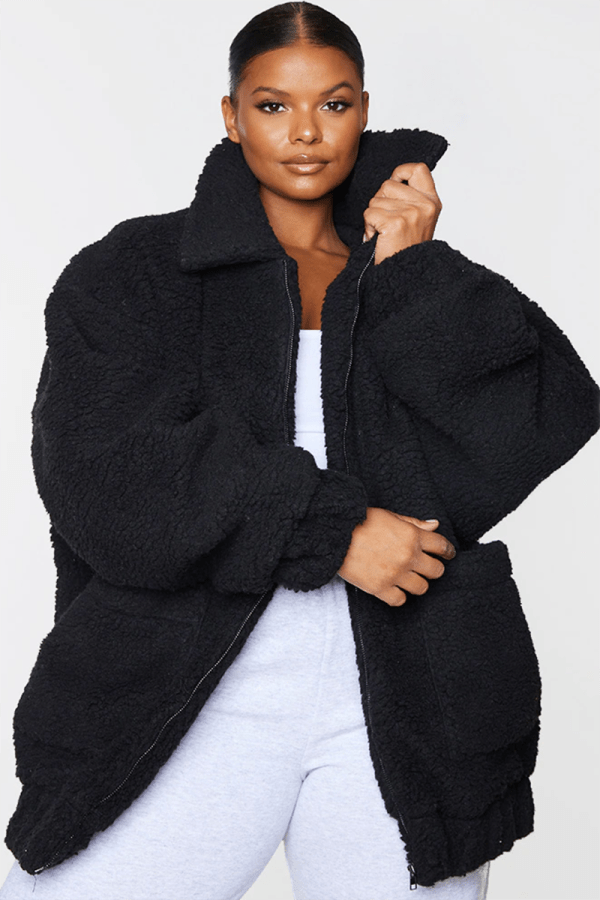 A plus-size model wearing an oversized black teddy jacket.