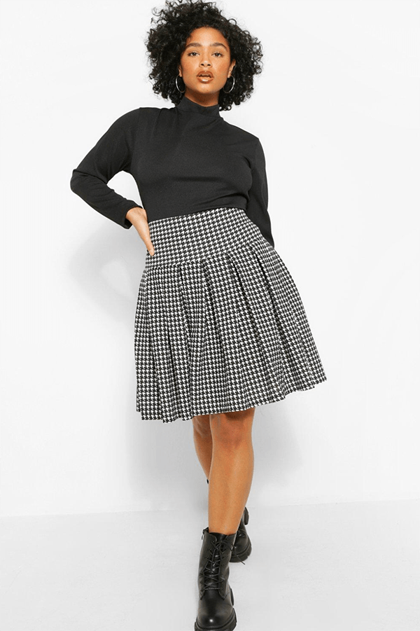 A plus-size model wearing a houndstooth tennis skirt.