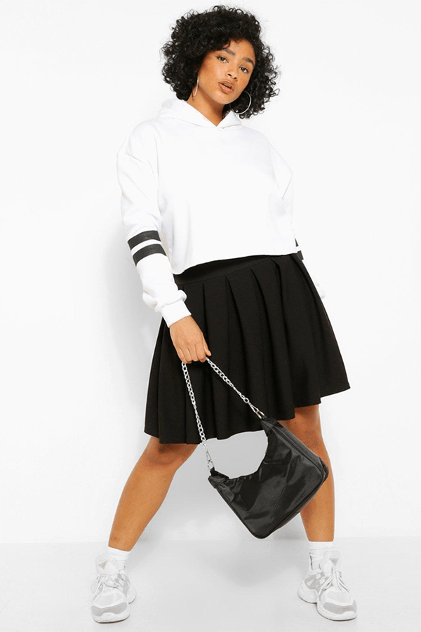 A plus-size model wearing a black tennis skirt.