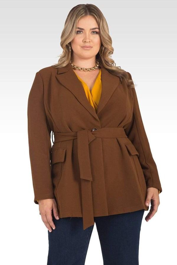 A plus-size model wearing a brown wrap blazer.