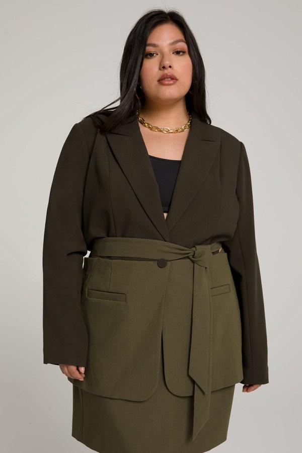 A plus-size model wearing an olive green colorblock wrap blazer.