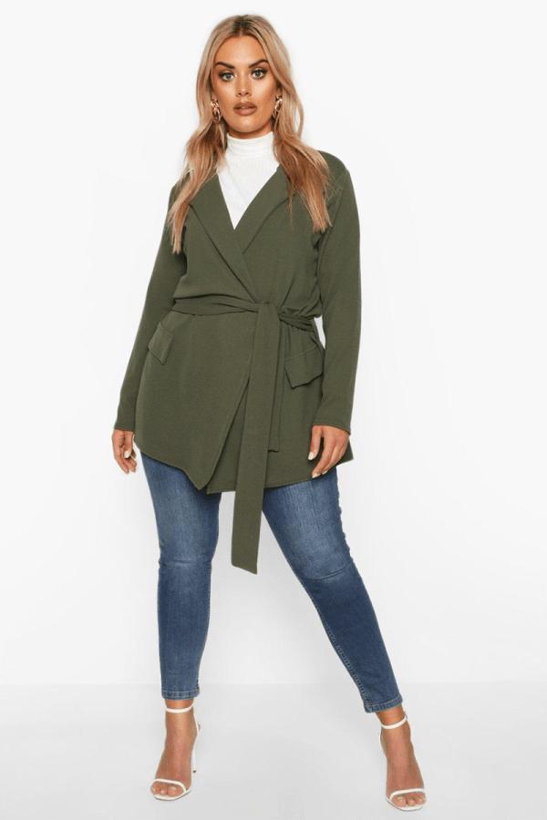 A plus-size model wearing an olive green wrap blazer.