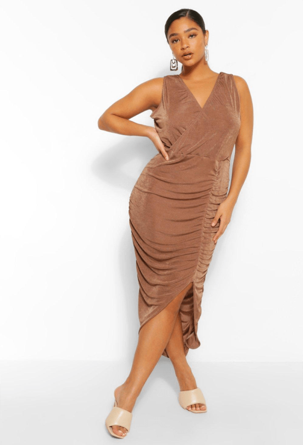 A plus-size model wearing a sexy brown midi dress.