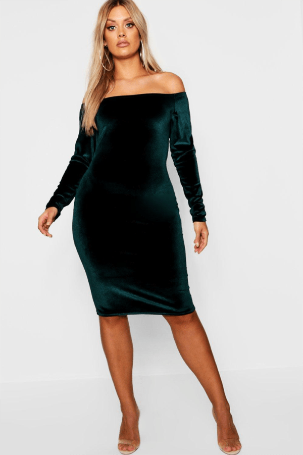 A plus-size model wearing a sexy green velvet off-the-shoulder dress.