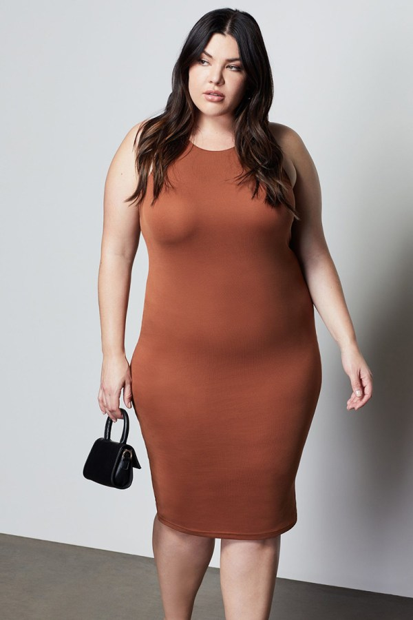 A plus-size model wearing a sexy brown bodycon dress.