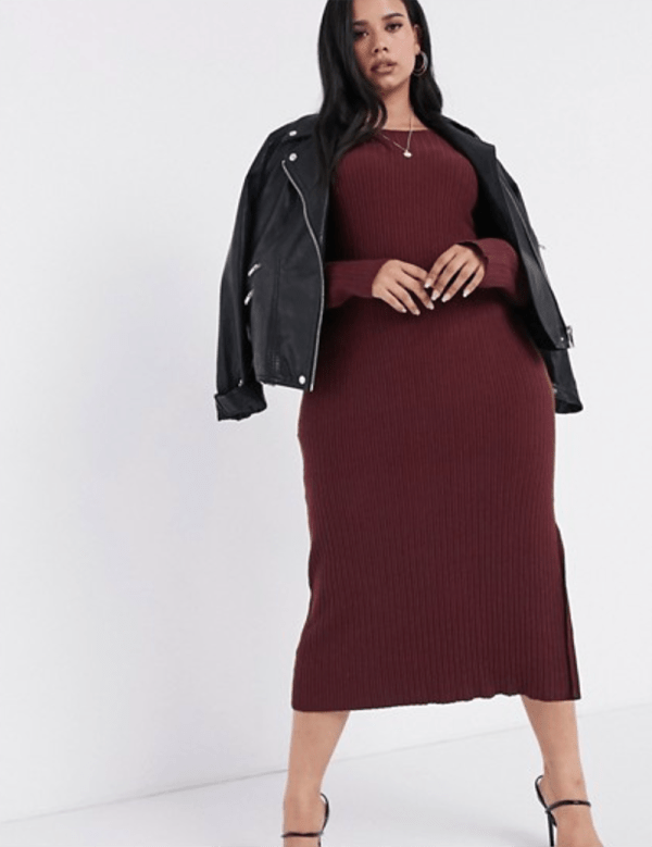 A plus-size model wearing a sexy burgundy sweater dress.