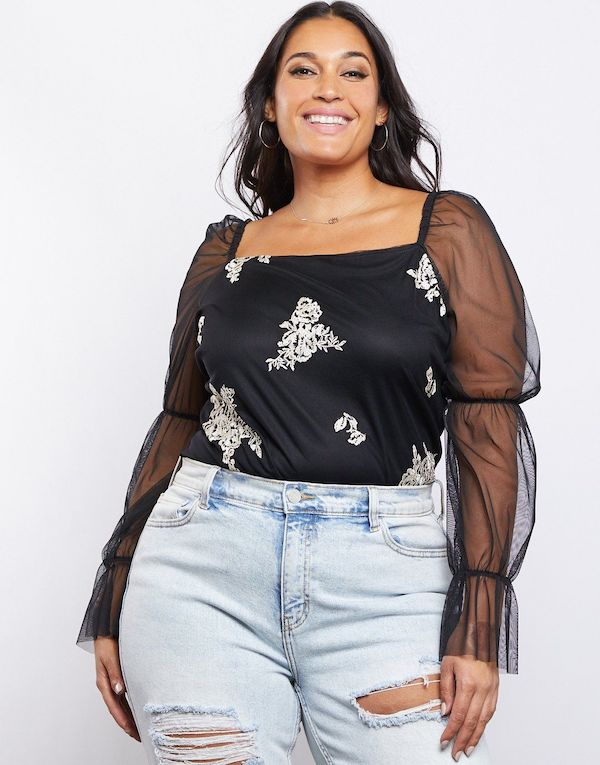 A plus-size model from 2020AVE wearing a black and white sheer-sleeve blouse.