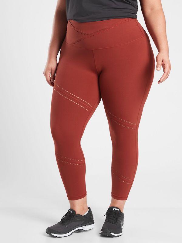 A plus-size model from Athleta wearing burnt orange leggings.