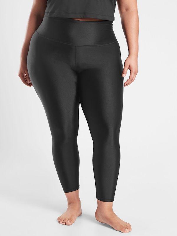 A plus-size model from Athleta wearing black leggings.