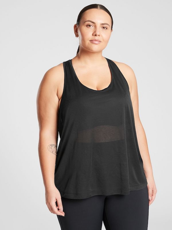A plus-size model from Athleta wearing a black mesh tank top.