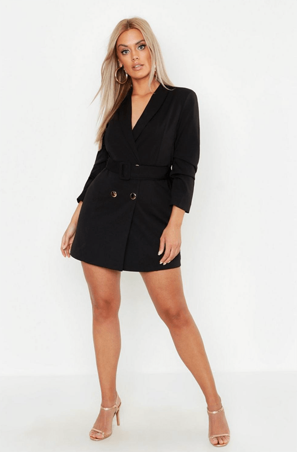 A plus-size model wearing a black blazer dress, which will be on sale at Boohoo's 2020 Black Friday sale.
