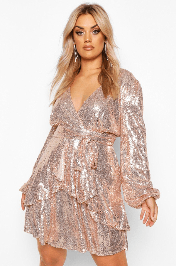 A plus-size model wearing a pink sequin dress, which will be on sale at Boohoo's 2020 Black Friday sale.