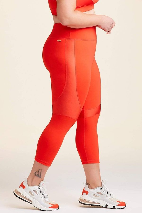 A plus-size model from CoEdition's Black Friday sale wearing orange leggings.