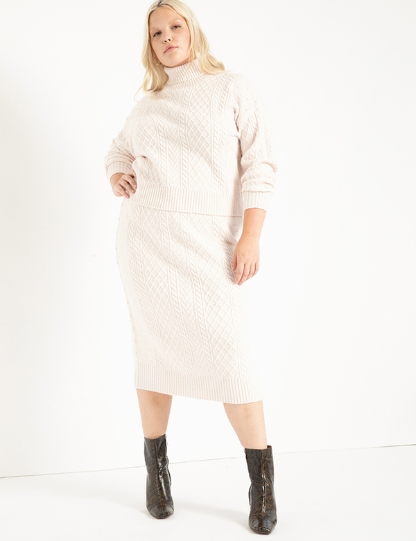 A plus-size model wearing a white knit midi skirt, which will be marked down at Eloquii's 2020 Black Friday sale.