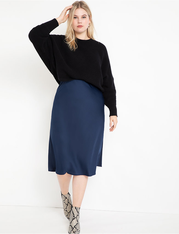 A plus-size model wearing a navy satin slip skirt, which will be marked down at Eloquii's 2020 Black Friday sale.
