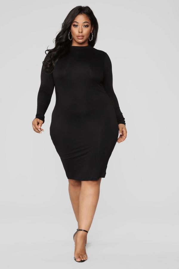 A plus-size model from Fashion Nova wearing a black midi bodycon dress.