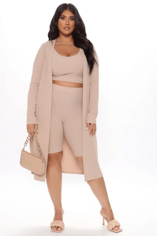 A plus-size model from Fashion Nova wearing a tan lounge short set.