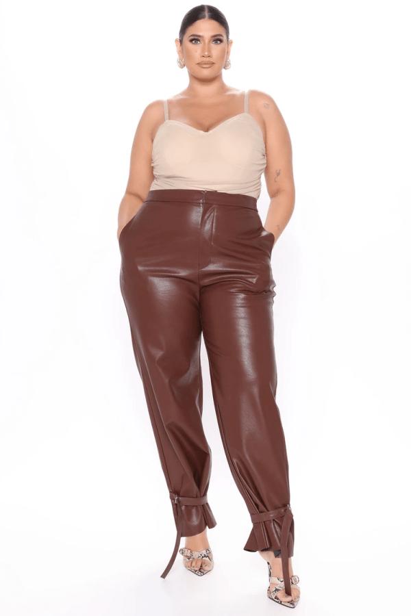 A plus-size model from Fashion Nova wearing brown faux leather pants.