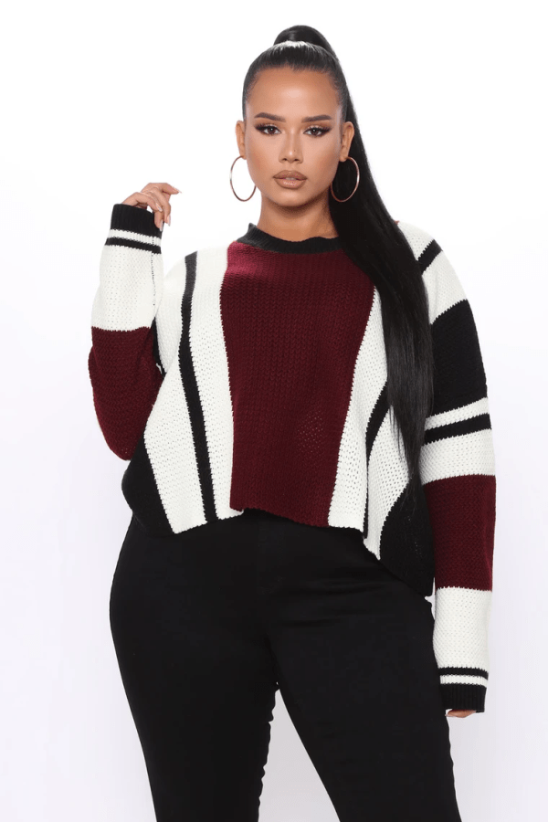 A plus-size model from Fashion Nova wearing a red, black, and white sweater.