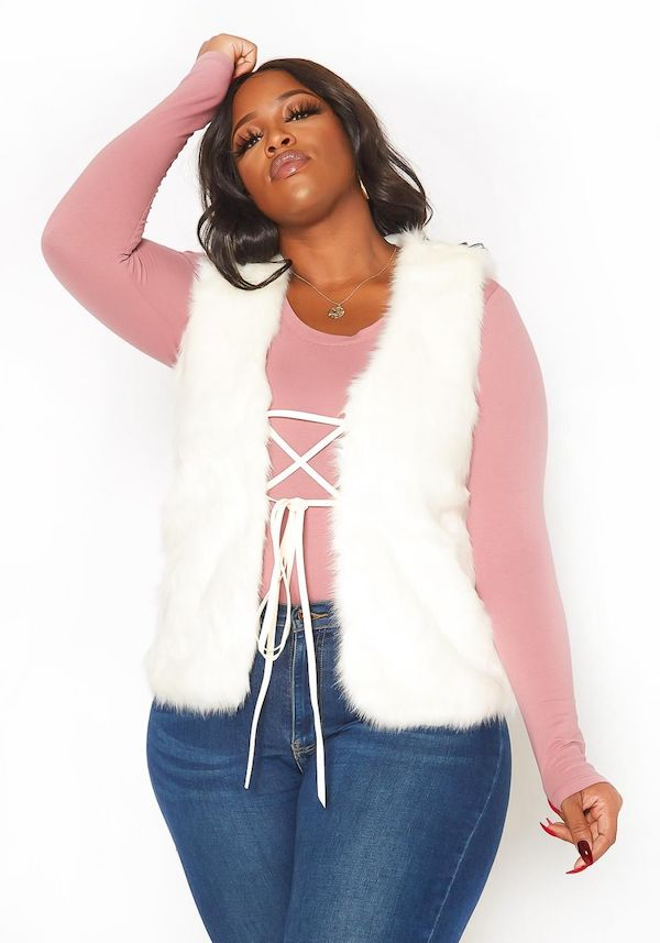 A plus-size model wearing a white faux fur vest from Asoph.