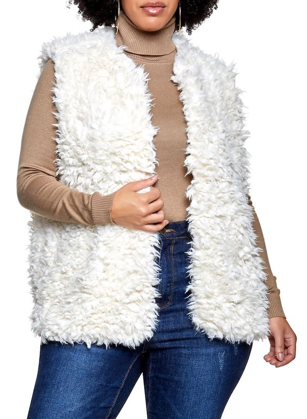 A plus-size model wearing a white faux fur vest.