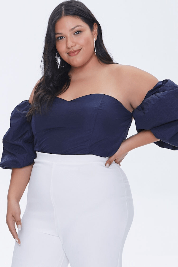 A plus-size model wearing a navy puff sleeve blouse.