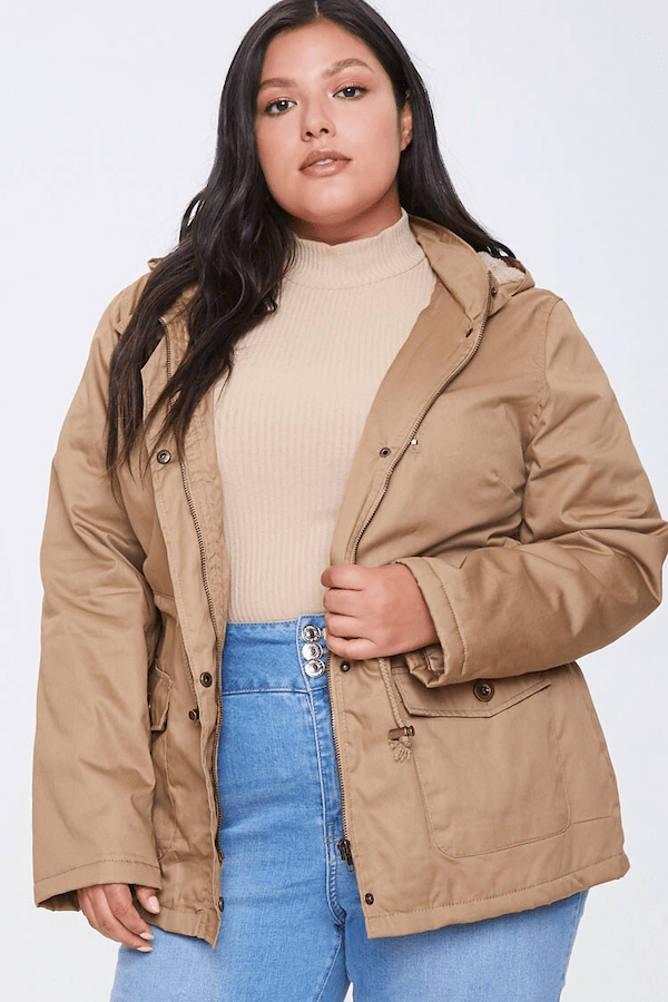 A plus-size model wearing a tan puffer coat.