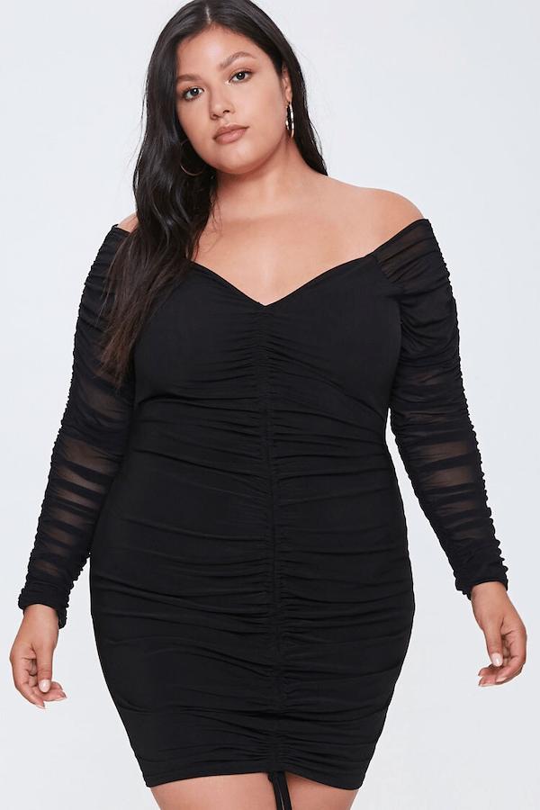 A plus-size model wearing a black mini dress.
